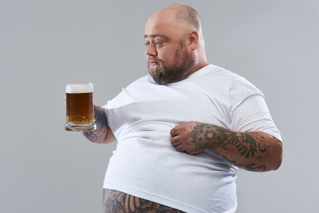 Isolated on the grey background photo of fat bearded man scratching his belly and looking attentively at the glass of beer in his hand