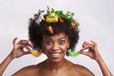 Fashion look and human emotions. Close up portrait of expressive smiling afro american lady holding her odd fish earrings out while staying isolated on white background