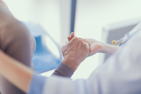 Focus on close-up of doctor holding patient hand while embracing her. Aged lady is getting medical treatment in clinic Stockfoto