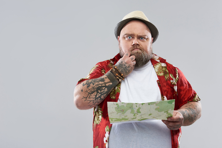 Feeling lost. Curious fat bearded traveler in bright Hawaiian shirt standing isolated on the grey background and scratching his beard while holding a map. Copy space on the left side Stock Photo