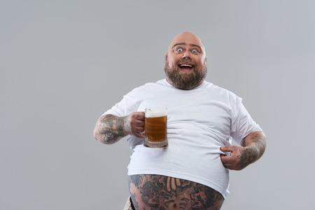 Hombre gordo gracioso positivo con cuerpo tatuado con camiseta blanca y sonriendo mientras sostiene un gran vaso de cerveza aislado en el fondo gris