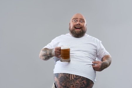 Positive funny fat man with tattooed body wearing white T-shirt and smiling while holding a big glass of beer isolated on the grey background Foto de archivo
