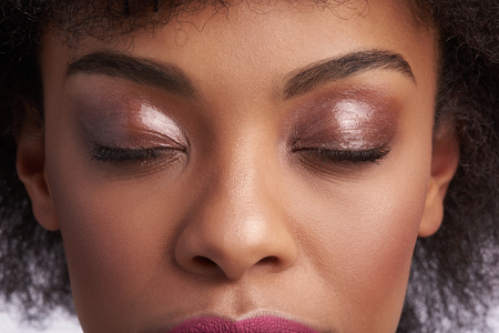 Fashion make up and natural look. Close up upper face portrait of sensual calm afro american woman with nude shimmery eyeshadow on closing eyes