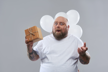 Happy bearded fat man standing with a present in his hands and having white balloons behind his back Banco de Imagens