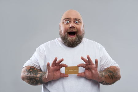 Waist up of funny fat man expressing excitement and opening his mouth while being isolated on the grey background and holding a gold card