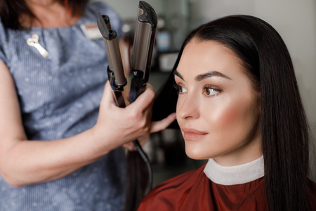 Focus on profile portrait of positive lady spending time at stylist. Professional is standing and holding curling iron for fixing