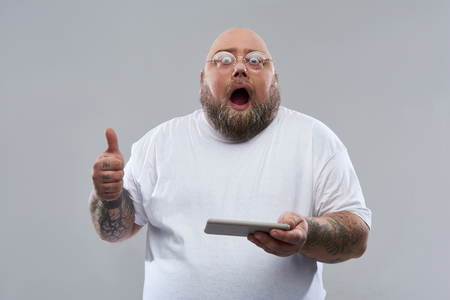 Waist up isolated on the grey background image of excited bearded fat man opening his mouth and putting thumb up while holding a modern smartphone 写真素材