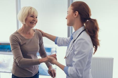 Concéntrese en la mujer madura sonriente con muletas mientras agradece y se despide de la doctora. Están parados juntos en el consultorio médico y amablemente tomados de la mano.