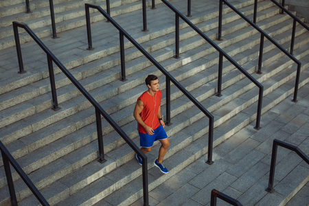 Full length portrait calm young sportsman running on stairs while listening music with headsets outdoor