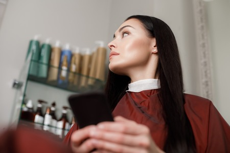 Low angle with focus on relaxed woman wearing protective gown and sitting in chair. She is having hair treatment in beauty studio and using mobile phone during it