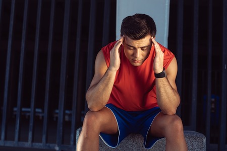 Portrait of depressed man touching head with arm while feeling pain after training Standard-Bild
