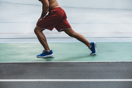 Close up male legs doing physical exercise. He wearing contemporary shorts and sneakers Stock Photo