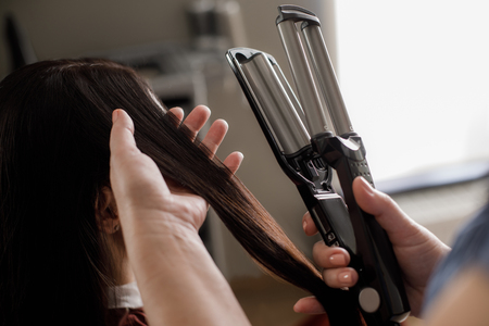 Top view close-up of hairdresser hands holding curling iron and client lock. She is using device for waving female hair in beauty salon