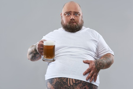 Fat middle aged bearded man putting hand on the belly while standing isolated on the grey background with a glass of beer