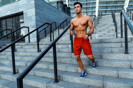 Full length portrait of calm stripped to waist male athlete with attractive body running on stairs outside Stock fotó