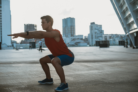 Full length side view concentrated young man doing squats while locating outside