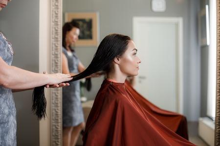 Taillenporträt eines schönen Mädchens, das auf einem Stuhl sitzt, während der Meister der Frisuren professionell ihr langes Haar hält
