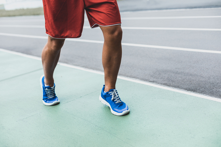 Never give up. Close up male runner legs in contemporary sneakers moving on road