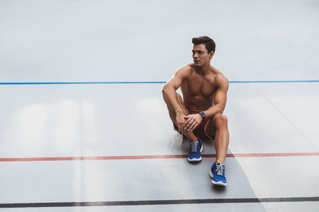 Full length portrait of thoughtful stripped to waist man athlete with attractive body having relax after training Stock Photo