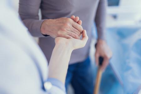 Centrarse en el primer plano de la vista superior de la mujer de apoyo del trabajador médico. El paciente usa muletas y se apoya en el brazo del médico mientras se conectan las palmas