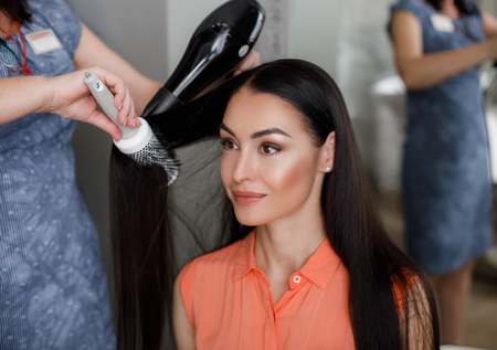 Smiling lady is sitting in front of mirror in beauty salon. Female stylist is standing beside and drying her hair with fan and brush