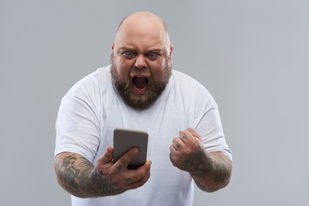 Waist up of fat bearded man expressing anger and shouting while looking at the screen of smartphone in his hands