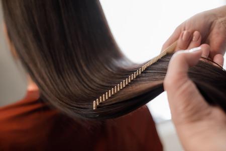 Nahaufnahme des Friseurs, der beim Kämmen mit der Haarbürste Haarstyling für die Frau macht Standard-Bild