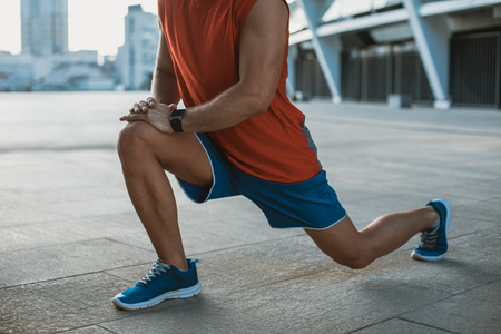 Male athlete doing physical exercise while situating outdoor during day
