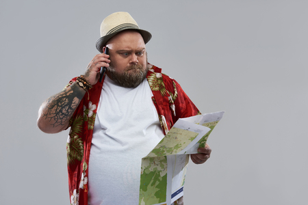558b54823 Concentrated fat bearded tourist in Hawaiian shirt standing alone isolated  on the grey background and frowning