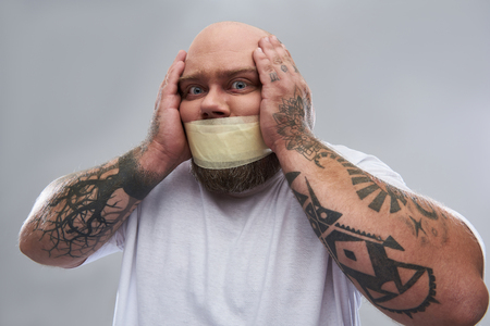 Having problems. Close up image of tattooed fat man having masking tape on his mouth and feeling unwell while touching his head isolated on the grey background Imagens - 116484161