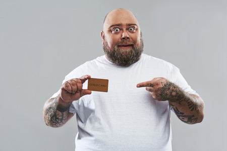 Waist up of happy bearded man standing alone against the grey background and smiling while pointing to the gold card in his hands Stockfoto