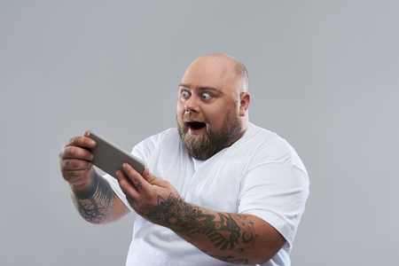 Isolated on grey background photo of fat bearded man with tattooed arms holding modern smartphone and feeling excited while looking at the screen of smartphone Stock fotó