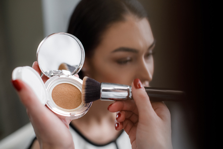 Close up of makeup artist using compact powder to matte skin and equalizing tone in beauty salon