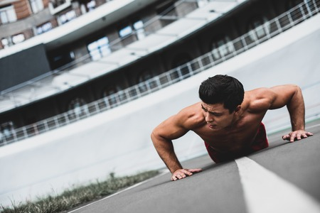 Portrait of serene man with attractive body doing physical exercises on stadium while watching away outdoor