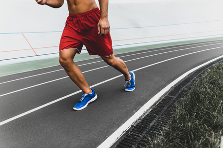 Stripped to waist man running while wearing contemporary sport clothes outdoor