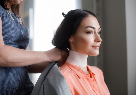 Delighted lady is relaxing during hair treatment in salon. She is sitting while stylist is standing behind Stock Photo