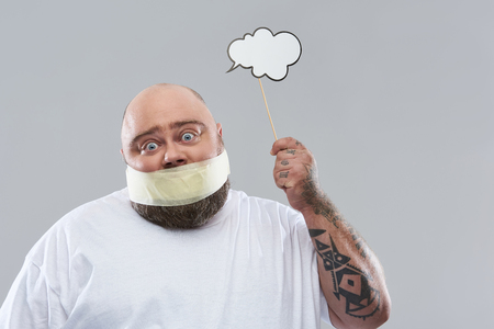 Saying nothing. Close up of fat surprised man putting eyebrows up while holding thought cloud near his head and having masking tape on the mouth