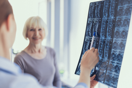 Focus on spine X-ray being held by specialist in clinic. She is pointing with pen at it and discussing with smiling mature lady who is standing beside. Copy space in left side