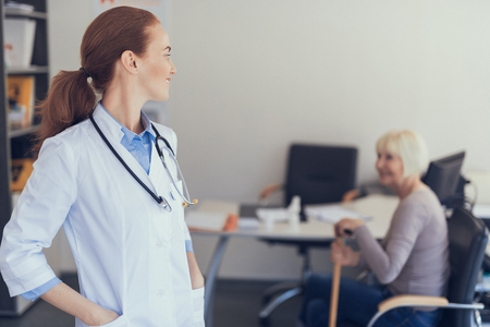 Focus on grinning female doctor standing and looking back at mature woman. She is sitting in chair near working table with computer while using crutch. Copy space in right side