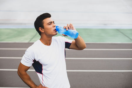 Portrait of concentrated young man drinking bottle of water after training on athletic field. Orderly guy during rest concept Stock Photo