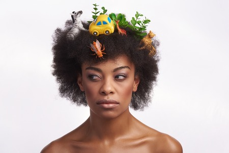 I dont trust you. Close up portrait of pretty afro american woman rolling her eyes aside with suspicious while staying isolated on white with odd safari hairstyle 免版税图像