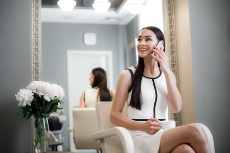 Lovely young woman spending time in dressing room and smiling while sitting in armchair