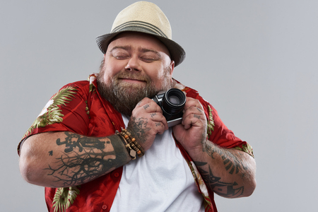 Favorite camera. Pretty funny bearded tourist in Hawaiian shirt smiling and closing his eyes while standing alone isolated on the grey background and gently pressing his retro camera to the chest Stock fotó