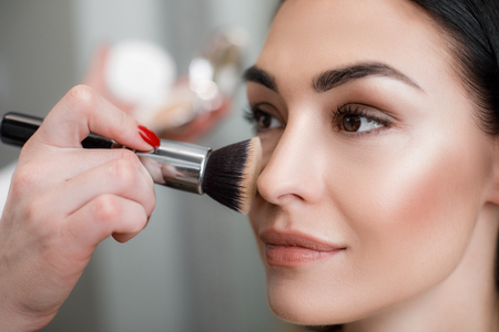 Close up of makeup artist applying light layer of matting powder while using professional brush for lady Stock Photo