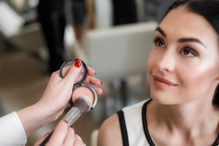 Close up of makeup artist emphasizing cheekbones while using peach blush in beauty salon