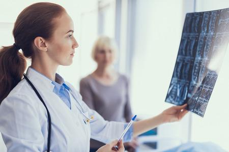 Concentrati sul ritratto di profilo del medico concentrato che tiene la radiografia e la guarda. La donna è in piedi vicino e aspetta i risultati. Copia spazio sul lato destro