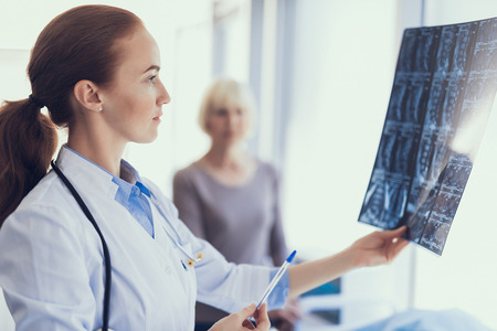 Focus on profile portrait of concentrated doctor holding radiography and looking at it. Woman is standing near and waiting for results. Copy space in right side