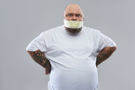 Keep silent. Offended angry fat man standing akimbo isolated on the grey background and frowning while having his mouth closed with masking tape