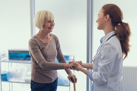 Focus on joyful lady standing with crutch in medical clinic. Kind female specialist is holding her hand being glad to see patient Imagens - 116484093