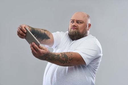 Fat bearded man with tattooed arms standing isolated on the grey background and making funny faces while holding modern smartphone